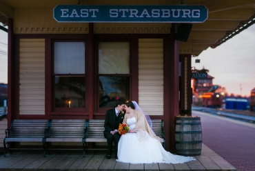 Bride and groom on bench at Strasburg Train Station .